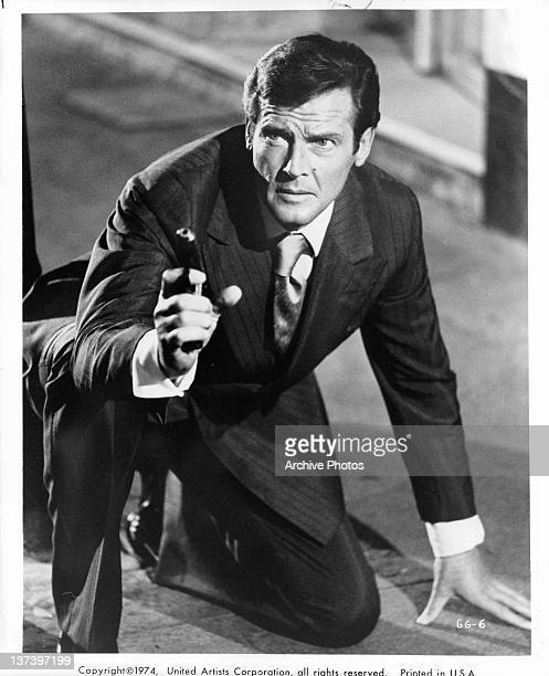 Roger Moore on his knees in a suit pointing a gun in a scene from the film 'The Man With The Golden Gun' 1974