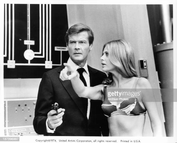 Roger Moore pointing a gun and Britt Ekland pointing her finger straight ahead in a scene from the film 'The Man With The Golden Gun' 1974