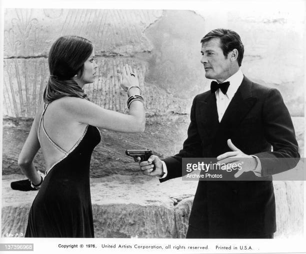 Roger Moore pointing a gun at Barbara Bach both wearing formal wear in a scene from the film 'The Spy Who Loved Me' 1977