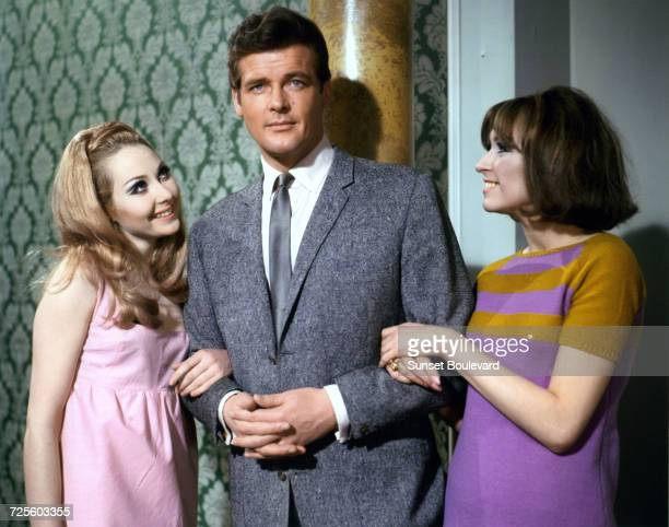 Roger Moore poses with two actresses in a promotional portrait for the TV series 'The Saint' circa 1967