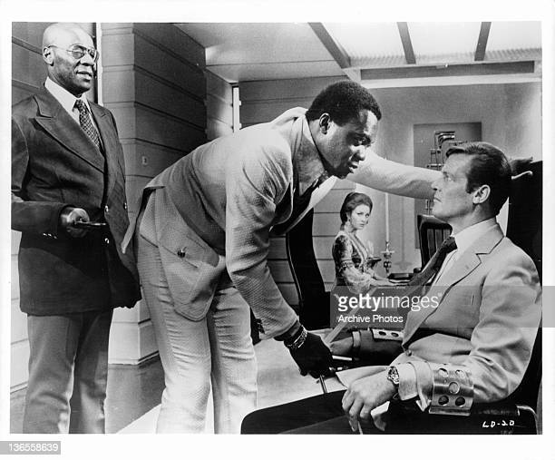 Roger Moore sitting in a chair with arm restraints while Yaphet Kotto stares at him closely face to face in a scene from the film 'Live And Let Die'...