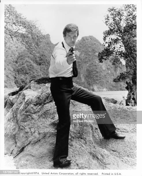 Roger Moore standing on a large rock pointing a gun in a scene from the film 'The Man With The Golden Gun' 1974