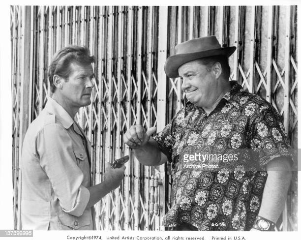 Roger Moore with a gun in his hand looking at actor Clifton James who is leaning against a metal gate in a scene from the film 'The Man With The...