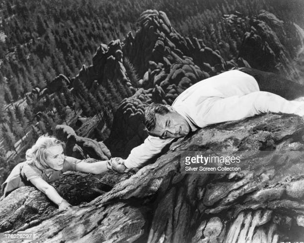 Roger O Thornhill played by Cary Grant and Eve Kendall played by Eva Marie Saint hanging from a cliff at Mount Rushmore in 'North By Northwest'...