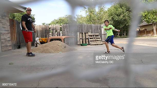 Roger Richards a production technician at the Pantex Plant nuclear weapons facility practices hockey with one of his three children in front of their...