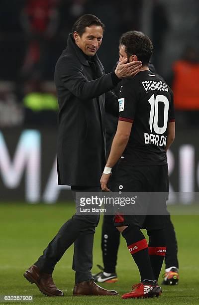 Roger Schmidt head coach of Leverkusen gongratulates goal scorers Hakan Calhanoglu after the Bundesliga match between Bayer 04 Leverkusen and Hertha...