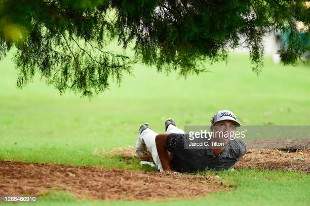 Roger Sloan of Canada inspects his lie on the ninth hole during the third round of the Wyndham Championship at Sedgefield Country Club on August 15,...
