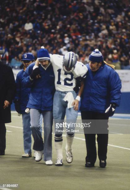 Roger Staubach of the Dallas Cowboys is helped off the field after an injury from a Minnesota Vikings' player during a game circa 1970