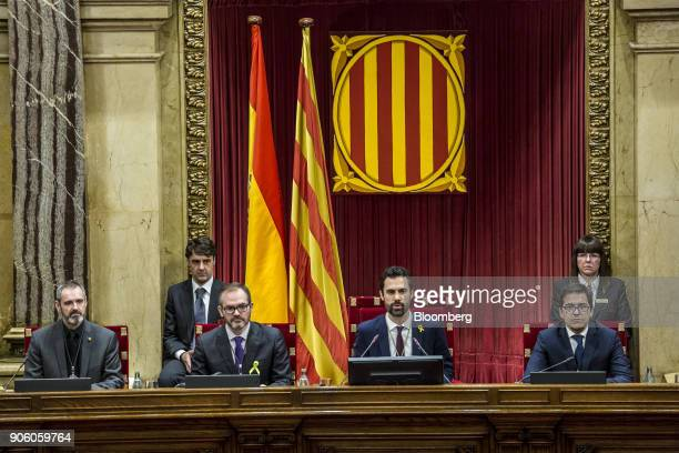 Roger Torrent new president of the Catalan parliament center speaks to lawmakers with fellow parliamentary board members from left Eusebi...