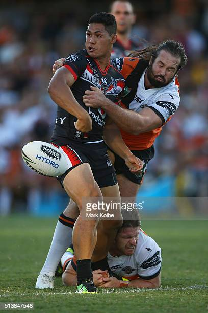 Roger TuivasaSheck of the Warriors flicks a pass out as he is tackled by Aaron Woods and Chris Lawrence of the Tigers during the round one NRL match...