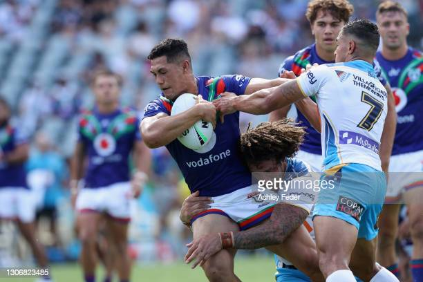 Roger Tuivasa-Sheck of the Warriors is tackled by Kevin Proctor of the Titans during the round one NRL match between the New Zealand Warriors and the...