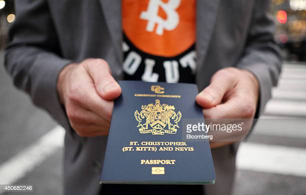 Roger Ver founder of Passports for Bitcoincom holds his passport as he poses for a photograph in the Shibuya district of Tokyo Japan on Wednesday...