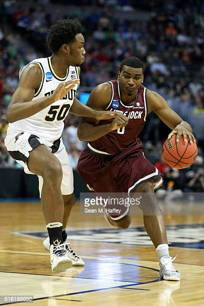 Roger Woods of the Arkansas Little Rock Trojans drives the ball around Caleb Swanigan of the Purdue Boilermakers during the first round of the 2016...