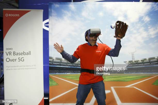 A Rogers Communications Inc employee tries to catch a baseball while wearing a virtual reality headset during a demonstration of 5G wireless network...