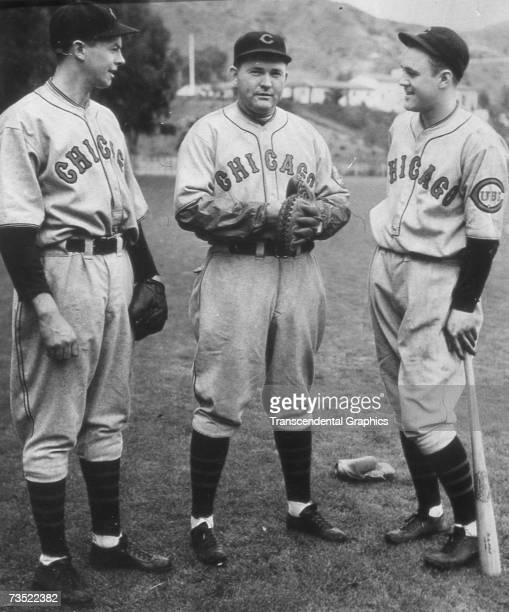 Rogers Hornsby second baseman and manager of the Chicago Cubs talks with Stan Hack left and Harry Taylor right before a game at Wrigley Field in 1932