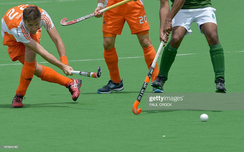 Rogier Hofman of The Netherlands (L) fires a ball under the feet of Shafqat Rasool of Pakistan (R) during their semi final match at the Men's Hockey Champions Trophy in Melbourne on December 8, 2012. IMAGE STRICTLY RESTRICTED TO EDITORIAL USE - STRICTLY NO COMMERCIAL USE AFP PHOTO/Paul CROCK