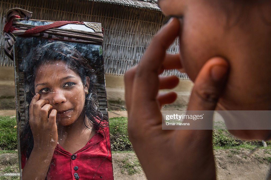 Rogina Darjee, 13 years old, puts on make-up while looking into a mirror in the Beldangi 2 refugee camp on March 14, 2015 in Beldangi, Nepal. More than 22,000 Bhutanese refugees still reside in the refugee camps set up in Nepal in the 1990s, after hundreds of thousands of Bhutanese fled the country following a campaign of ethnic cleansing by the Bhutanese Government against the country's ethnic Nepali population. After more than 20 years in Nepal, over 90% of the refugees have been successfully resettled in third countries, thanks to programs by UNHCR and IOM. Those remaining the camps are supported by several organizations that undertake a wide variety of projects. Helped by remittances sent back to Nepal by families already resettled in other countries, the refugees still in the camps have set up their own small businesses in the camps and the roads near them, roads which are also replete with Nepali-owned businesses who benefit directly from the refugees that are still waiting in Nepal to be resettled in third countries.