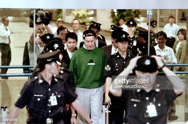 Rogue financial trader Nick Leeson arrives at Singapore's Changi airport surrounded by local police officers on November 23, 1995 after being...