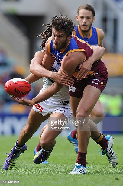 Rohan Bewick of the Lions handballs in the tackle during the round 22 AFL match between the Brisbane Lions and the Fremantle Dockers at The Gabba on...