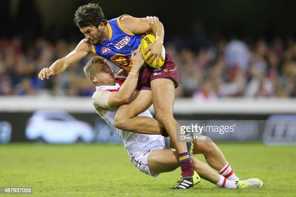 Rohan Bewick of the Lions is tackled by Dan Hanneberry of the Swans during the round seven AFL match between the Brisbane Lions and the Sydney Swans...