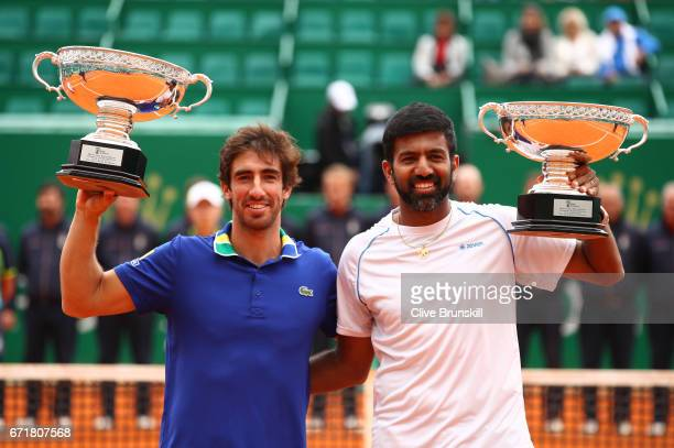 Rohan Bopanna of India and Pablo Cuevas of Uruguay hold aloft their winners trophies after their three set victory against Feliciano Lopez and Marc...