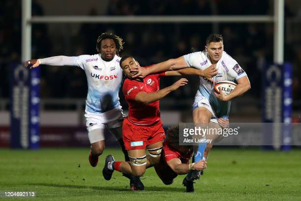 Rohan Janse van Rensburg of Sale Sharks holds of Andy Christie and Duncan Taylor of Saracens during the Premiership Rugby Cup SemiFinal match between...