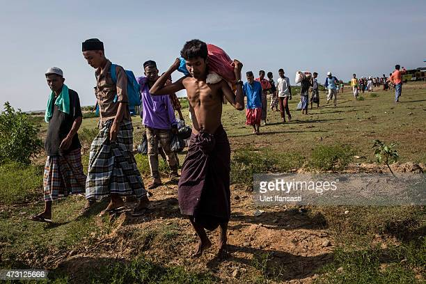 Rohingya and Bangladesh migrants carry their belongings after relocated to their new temporary shelter at Lapang village on May 13 2015 in Lhoksukon...