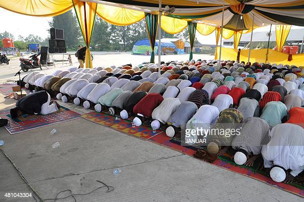 Rohingya and Bangladeshi migrants perform morning prayers celebrating Eid alFitr at a confinement camp for the migrants in Langsa located in...
