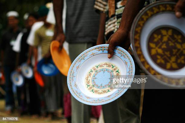 Rohingya boat people queue for lunch at a refugee camp in a district of the town of Idi Rayeuk on February 12, 2009 in Aceh province on Sumatra...