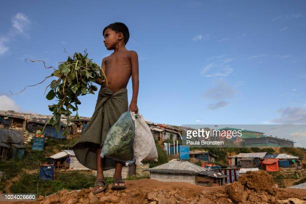 Rohingya boy carries greens for the family to cook in Kutupalong the largest refugee camp housing the Rohingya on August 26 2018 in Kutupalong Cox's...