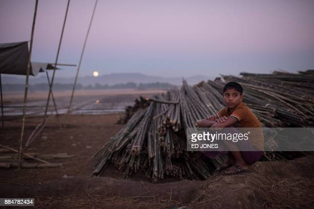 Rohingya boy sits next to bamboo used for building shelters at the Naybara refugee camp in Cox's Bazar on December 3 2017 Rohingya are still fleeing...