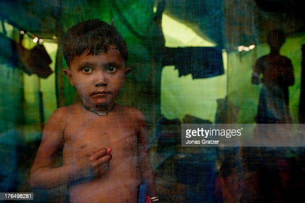 Rohingya boy stands behind a mosquito net inside a tent located in the IDP refugee camps of Sittwe. Sittwe now has over 125,000 people who are...