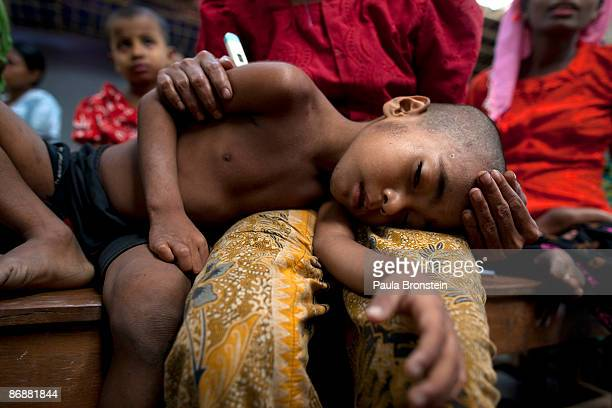 Rohingya boy suffering from malaria with a high fever is held by his mother at special clinic for malaria on May 4 2009 in Sittwe Arakan state...
