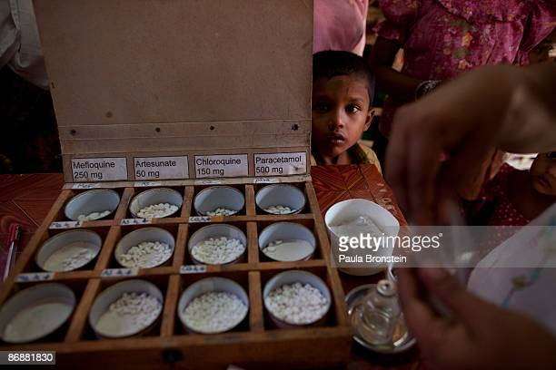 Rohingya boy watches as malaria medicine is given out to patients at special clinic for malaria on May 4, 2009 in Sittwe, Arakan state, Myanmar . The...