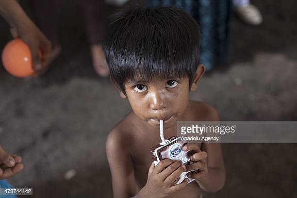 Rohingya child drinks milk received from local volunteers from Langsa in a warehouse in Kuala Langsa Port in Aceh province Indonesia on May 17 2015...