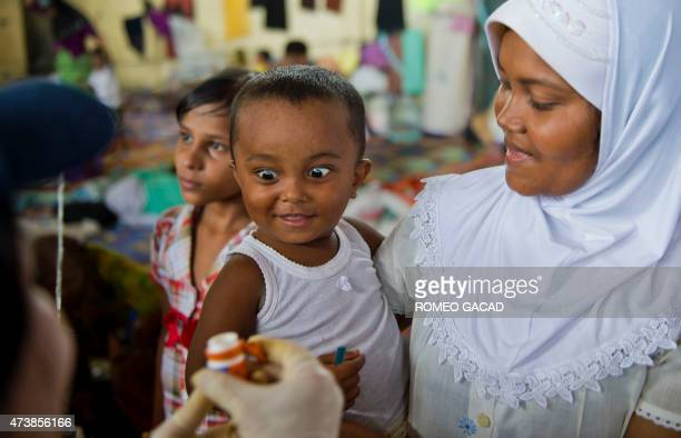 A Rohingya child from Myanmar receives vitamin A from a medical team from the International Organization for Migration while his mother looks on at...