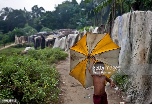 Rohingya child holds an umbrella in an informal settlement July 4 2015 in Shamlapur Bangladesh In the past months thousands of Rohingya have landed...