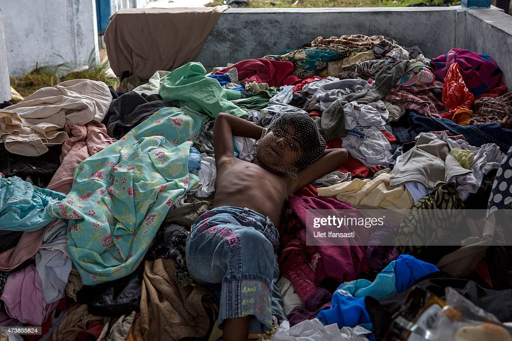 A Rohingya child sleeps on pile of used clothes at a temporary shelter on May 18, 2015 in Kuala Langsa, Aceh province, Indonesia. Hundreds of Myanmar's Rohingya refugees arrived in Indonesia on May 15, many requiring medical attention. Thousands more are believed to still be stranded at sea reportedly with no country in the region willing to take them in. Myanmar's Rohingya Muslim community have long been persecuted and marginalized by Myanmar's mostly Buddhist population.