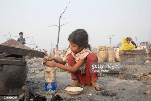 Rohingya children searching for their things, after a huge fire swept through a Rohingya refugee camp in southern Bangladesh on Monday, destroying...