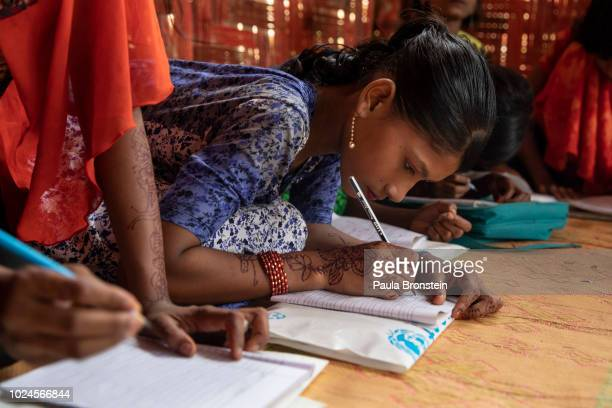 Rohingya children write in their books at a UNICEF learning center August 27 2018 in Balukhali camp Cox's Bazar Bangladesh UN investigators said on...