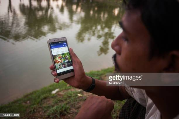 A Rohingya ethnic minority man looking facebook at his cell phone at a temporary makeshift camp after crossing over from Myanmar into the Bangladesh...