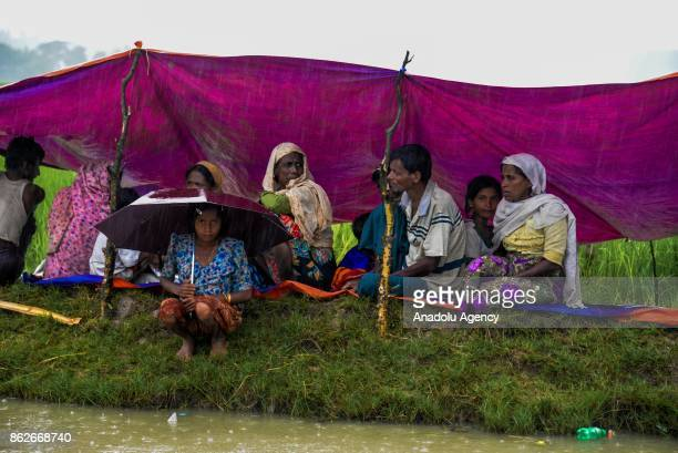 Rohingya family is sitting under a tarp to protect themselves from rain at Palong Khali in Coxs Bazar Bangladesh on October 17 2017 Rohingya people...