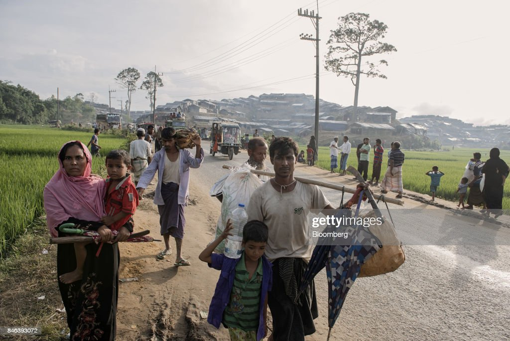 A Rohingya family walks past a newly set-up refugee camp at Balukhali in Cox's Bazar, Bangladesh, on Tuesday, Sept. 12, 2017. Myanmar's leaderAung San Suu Kyiis under attack over her response to a fresh round of violence that has seen more than 145,000minorityRohingyaMuslims flee into neighboring Bangladesh since last month. Photographer: Ismail Ferdous/Bloomberg via Getty Images