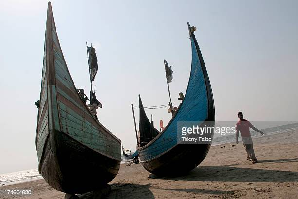 COX'S BAZAR BEACH BANGLADESH A Rohingya fisherman who has just returned from the sea walks past two boats on a Cox's Bazar area beach The Rohingya is...