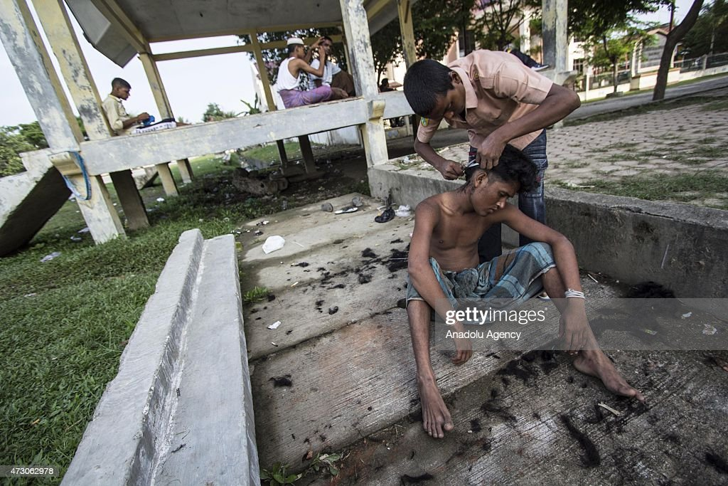 A Rohingya from Bangladesh and Myanmar cuts his hair at shelter at Matang Raya village on May 12, 2015 in Northern Aceh, Aceh, Indonesia. 573 Rohingya from Bangladesh and Myanmar were found stranded by Aceh fishermen on North Aceh sea. Rohingya were going to Malaysia with dozens of children and women.