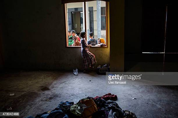 Rohingya girl migrant looks out through the window at a shelter on May 12 2015 in Lhoksukon Aceh province Indonesia Boats carrying over 500 of...
