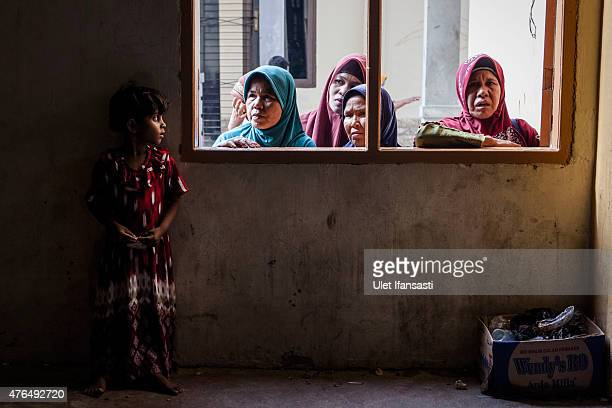 A Rohingya girl migrant stands as look out through the window at a shelter on May 12 2015 in Lhoksukon Aceh province Indonesia Boats carrying over...