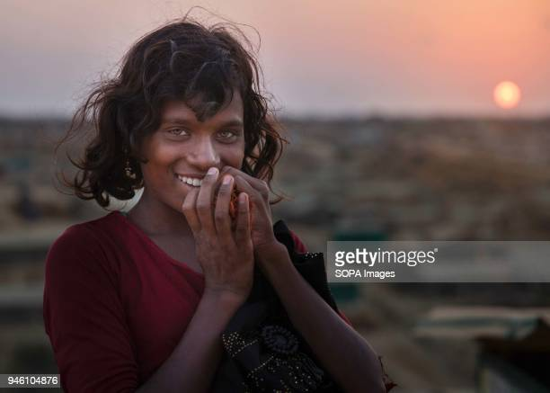 A Rohingya girl poses for a photograph at sunset in Kutupalong refugee camp There are now approximately 600000 Rohingya refugees in the Kutupalong...