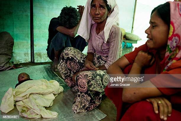 Rohingya girl's parents mourn for their daughter who has just died in the IDP refugee camps of Sittwe constant rain turned their earthen floors into...
