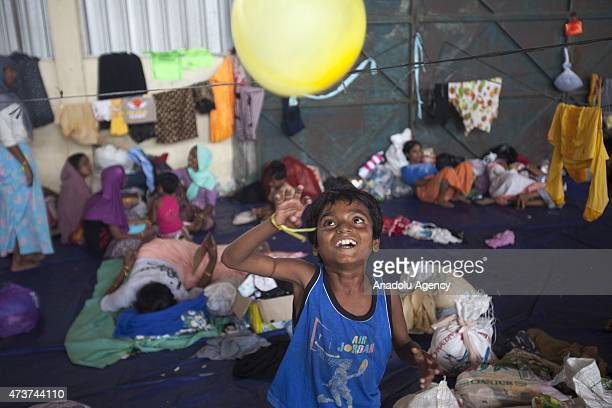 Rohingya kid plays with a balloon received from local volunteers from Langsa in a warehouse in Kuala Langsa Port in Langsa Aceh province Indonesia on...